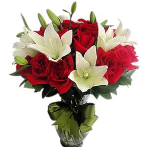 Rosas y lilis en florero de vidrio