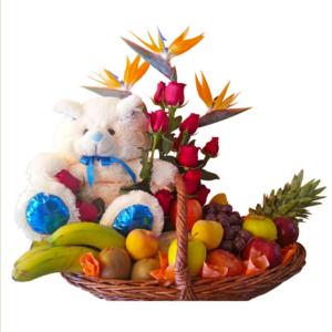Canasta de frutas con rosas y un oso de peluche